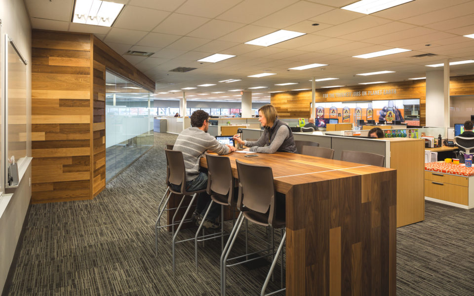 Two business people collaborate at large wooden desk