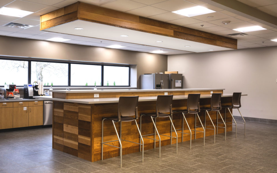 Corporate kitchen with large island featuring wood paneling