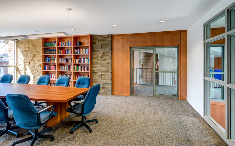 Conference room with wood paneling and bookshelf