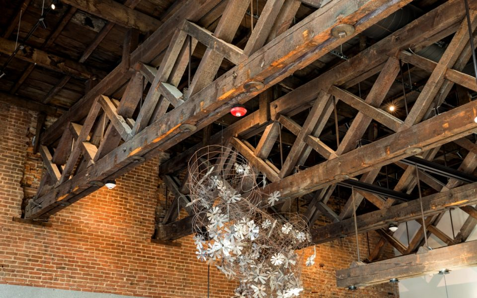 Large reclaimed wooden ceiling beams with wire and metal sculpture hanging from them