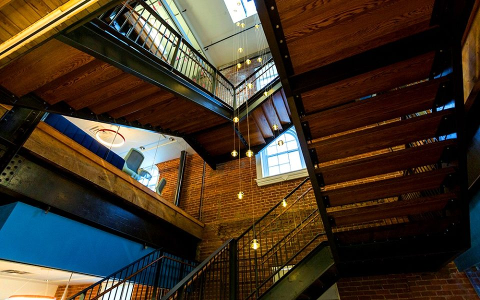 Upward view of large three-story staircase with light fixtures hanging down the center.
