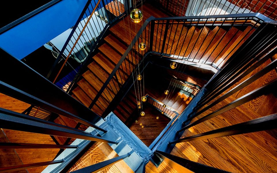 Downward view of large three-story wooden staircase with light fixtures dangling through center