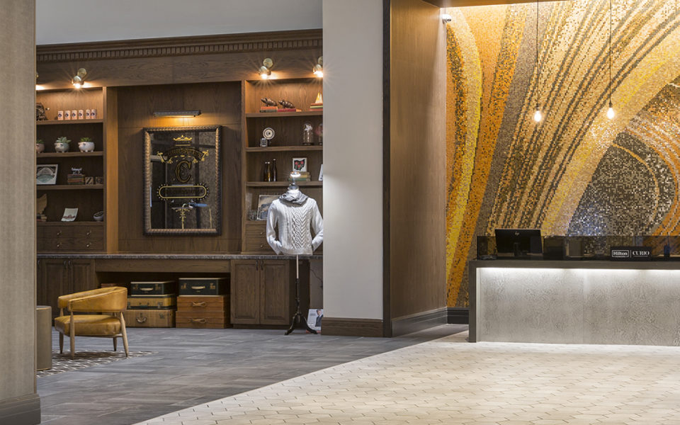 Large hotel lobby with stunning mosaic behind hospitality desk